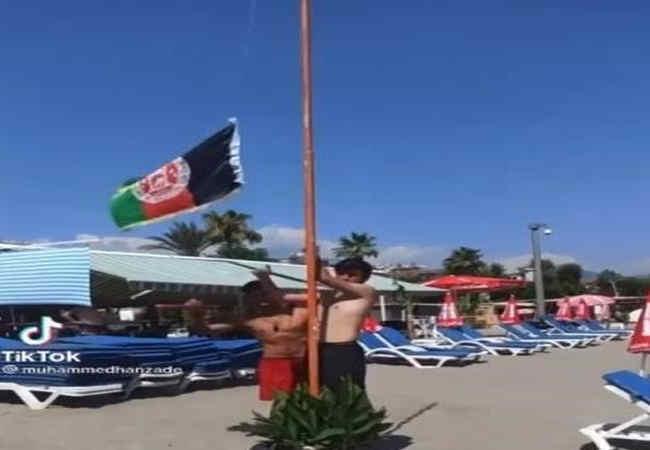 Antalya Plajinda Afganli Multeciler kendi bayragini diktiler.